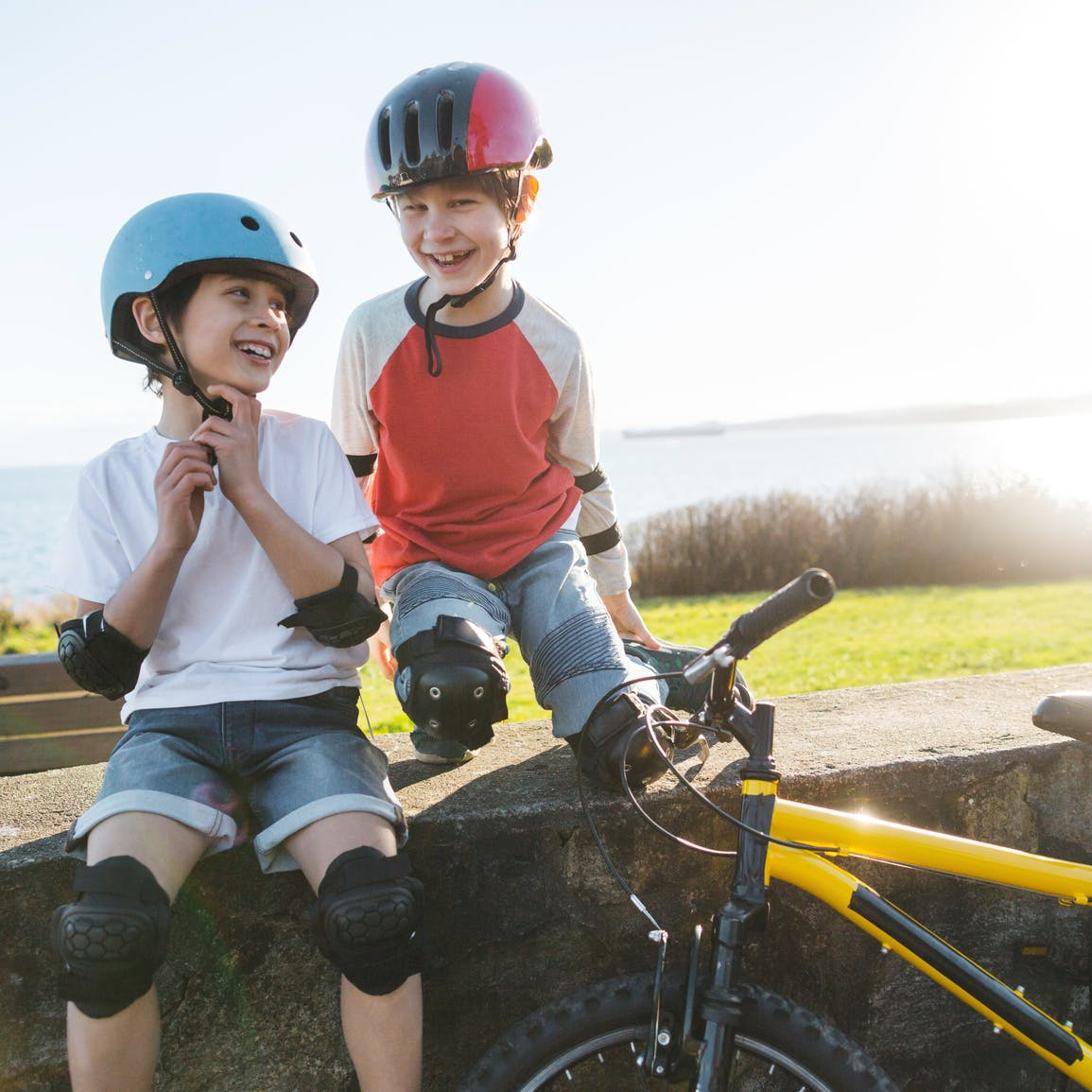Two children wearing bicycle helmets laughing with a bicycle