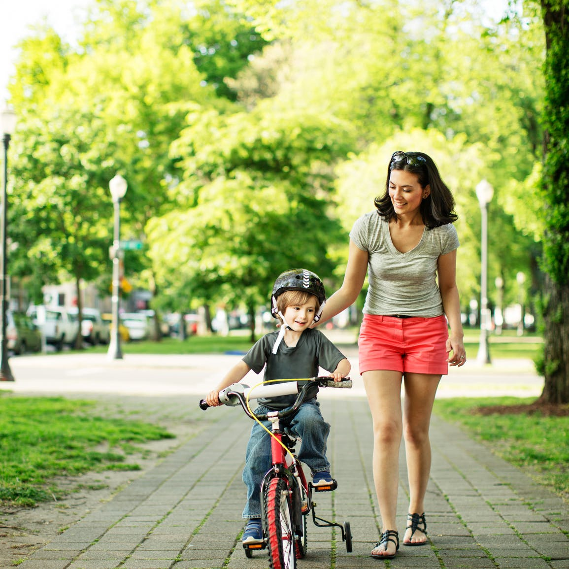 Child riding bicycle with help from mother