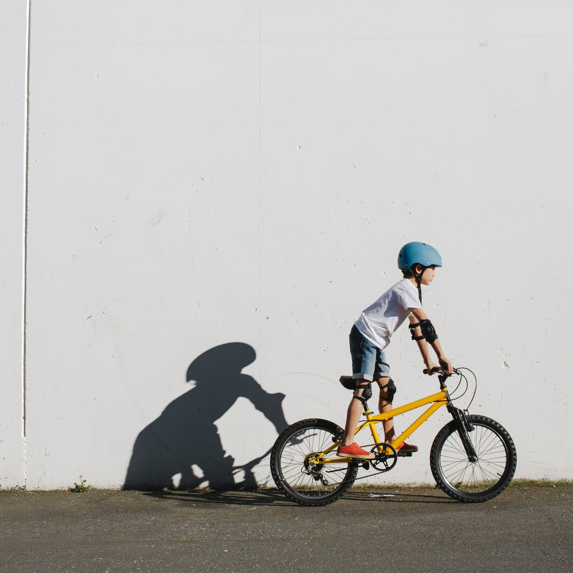 Child riding bicycle beside wall