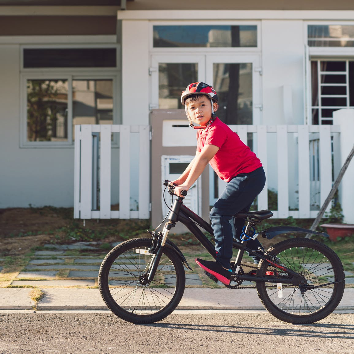Child wearing bicycle helmet riding bicycle beside house