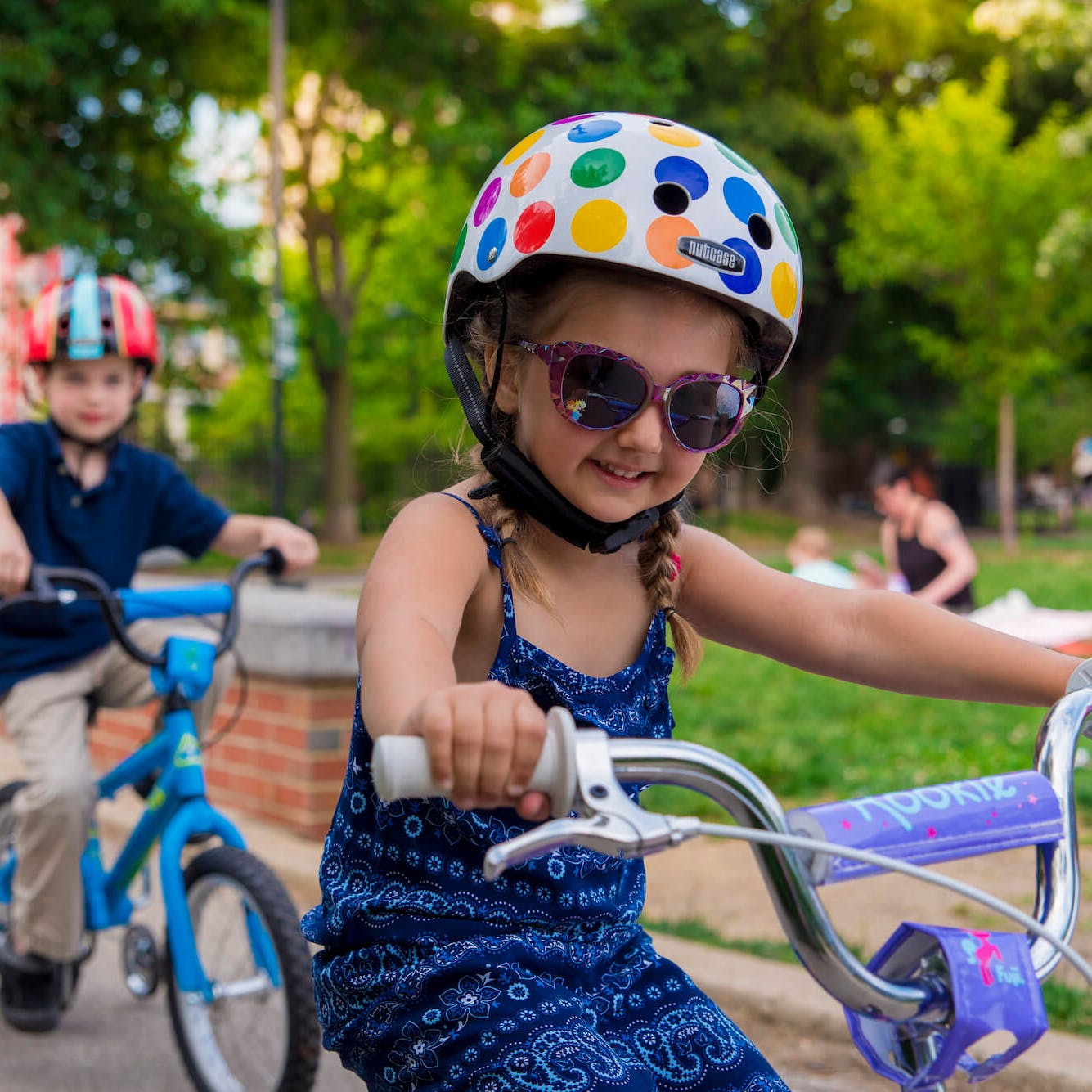A child wearing sunglasses leads the way for another child riding a bike with training wheels