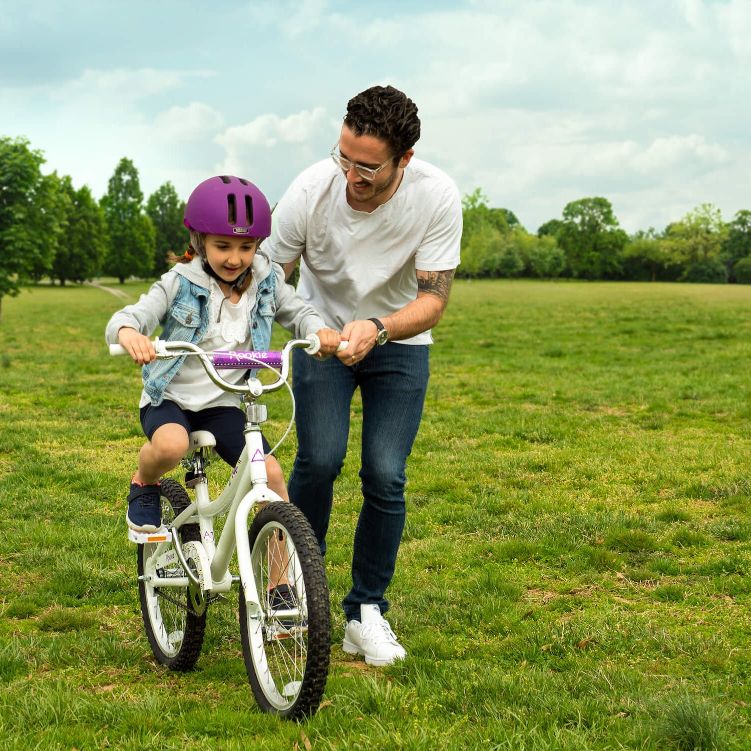 An adult in a white shirt helps a child in a jean vest learn to ride a bike in the middle of a grassy field