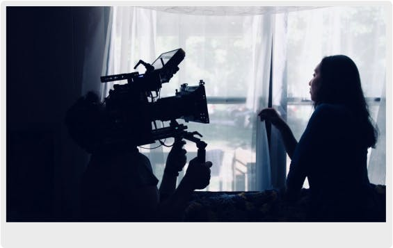 A camera operator filming a video of a woman looking out of a window