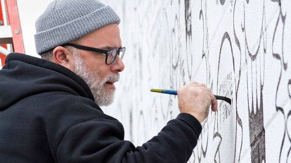 Artist Kevin Lyons painting a mural in Raleigh for Vans x truth