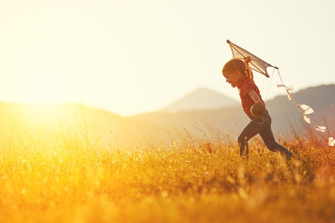 little girl running through field with kite in sunlight