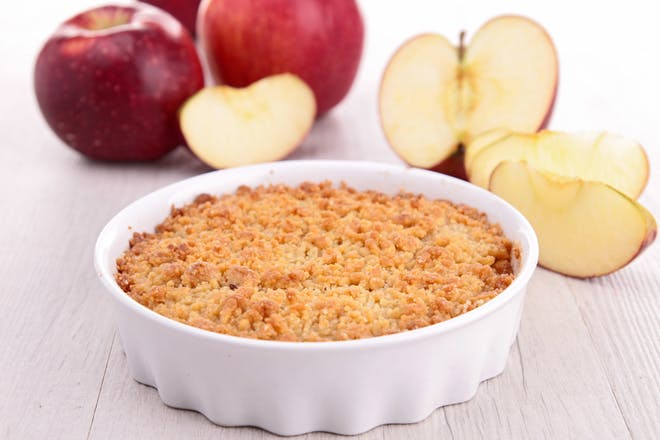 Apple crumble with apples on table
