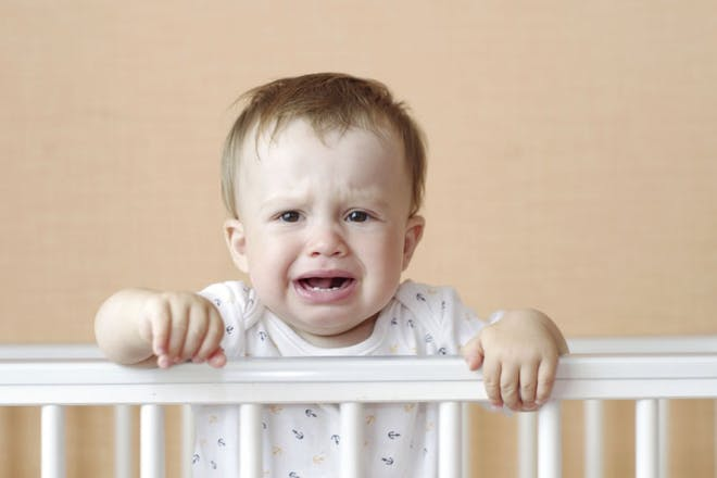 baby crying holding on to cot rail
