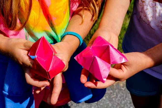 Two girls playing with paper fortune tellers
