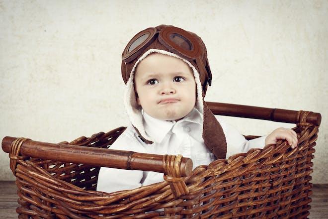 baby boy sitting in brown basket wearing brown vintage pilot helmet
