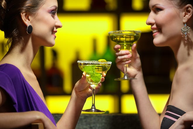 two women drinking cocktails at bar