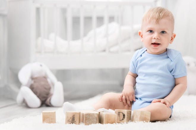 baby sitting up in his nursery next to building blocks