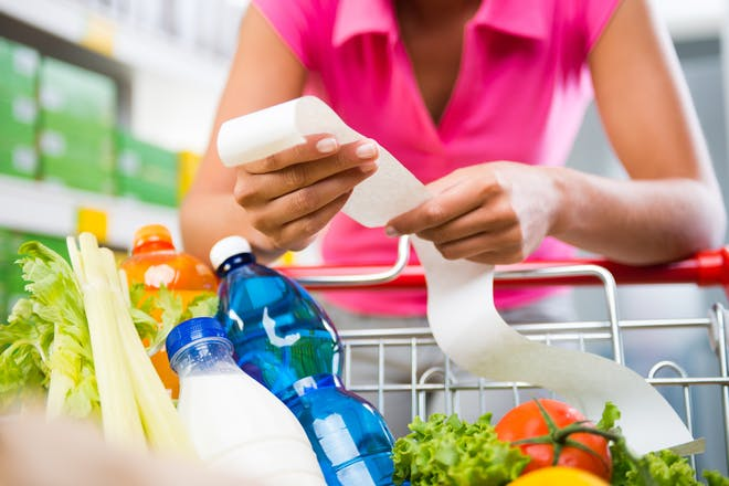 woman in supermarket with long receipt
