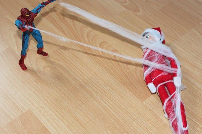 spiderman catching elf in web
