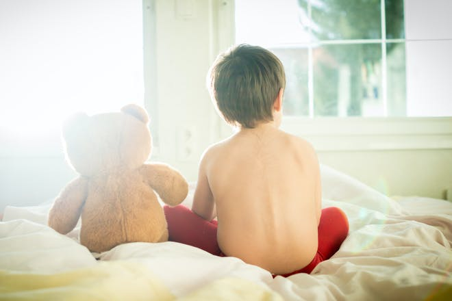child sat on bed with teddy bear