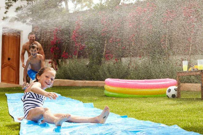 Kids playing on water mat in garden