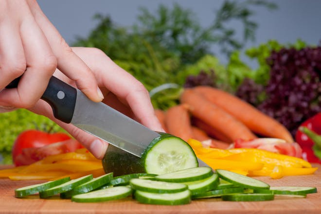 Women cutting cucumber with vegetables in the background