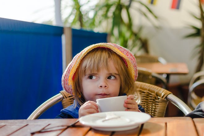 girl wearing hat drinking from tea cup