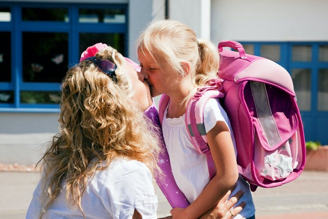 mother kissing girl with pink bag outside school