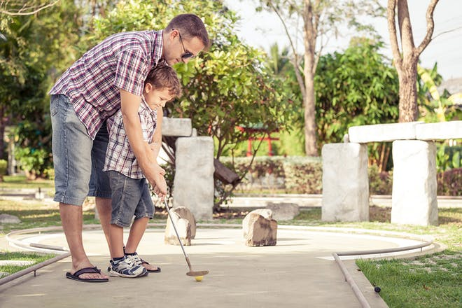 Dad and son playing mini golf