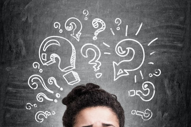 Confused african woman thinking about answers to her questions on chalkboard background