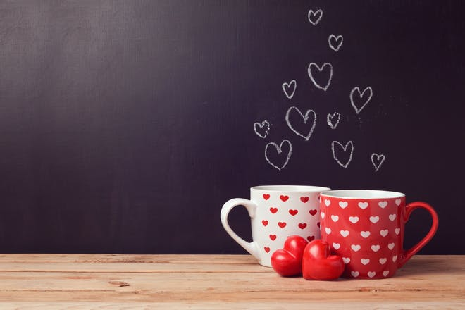 Two mugs with hearts on them, in front of blackboard with chalk hearts