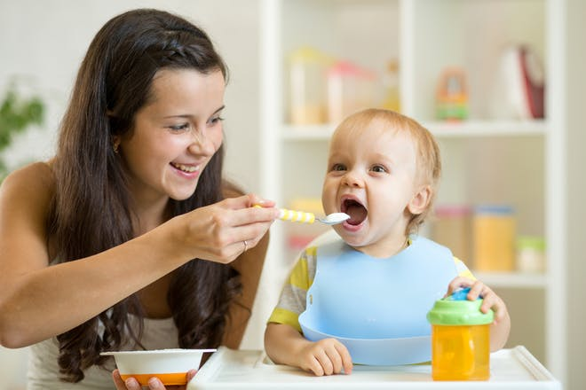 smiling woman spoon feeding her baby in high chair