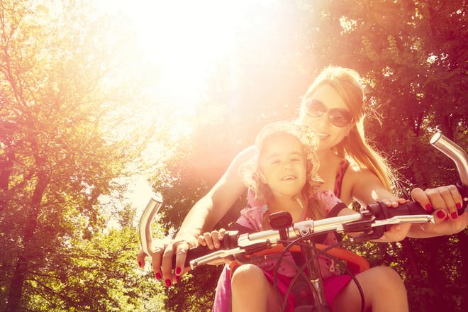 Mum and daughter riding a bike in the sunshine