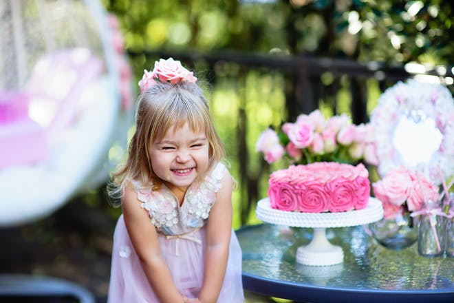 little girl smiling next to pink birthday cake