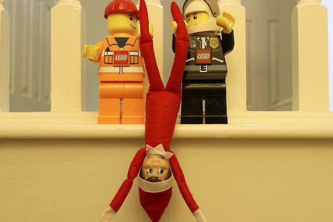 lego men holding elf upside down