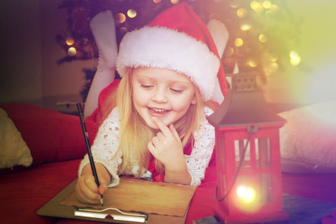 girl wearing christmas hat and writing a letter