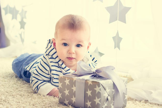 baby with gift wrapped in grey paper with white stars