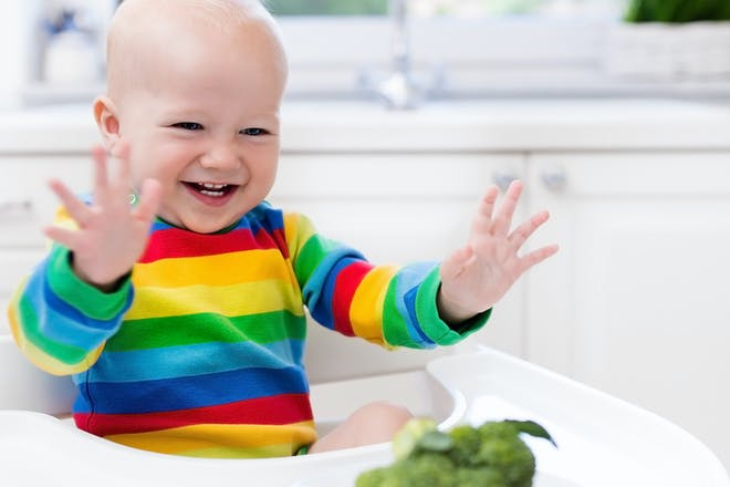 laughing baby sitting in high chair with whole broccoli on the tray
