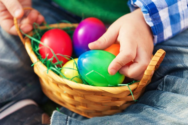 Child touching colourful eggs in a basket