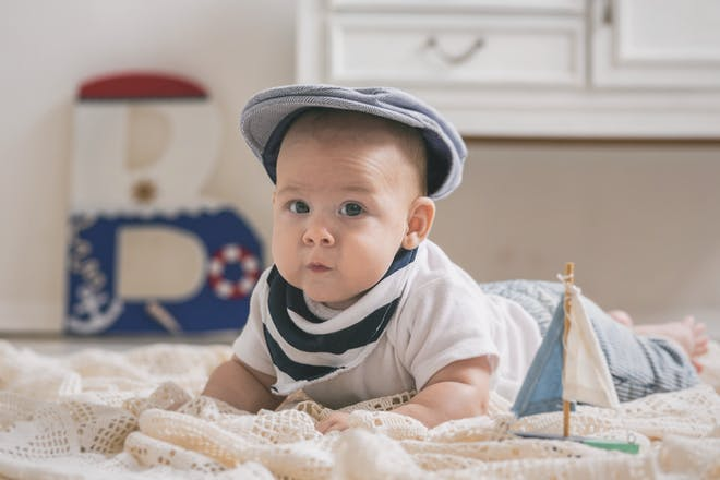 baby boy in a vintage clothes with a nautical themed room