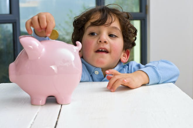child putting coin into pink piggy bank