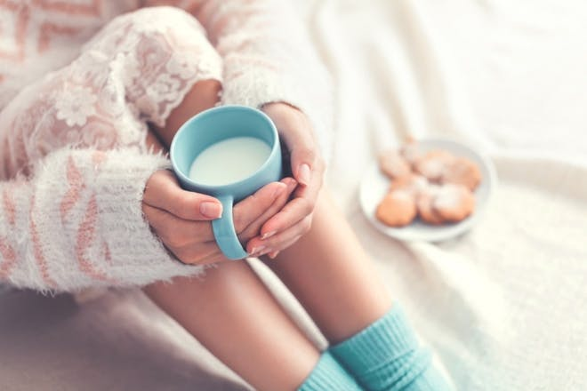 woman holding blue mug of milk