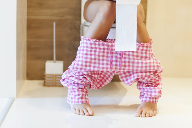 close up of woman's legs while sitting on toilet