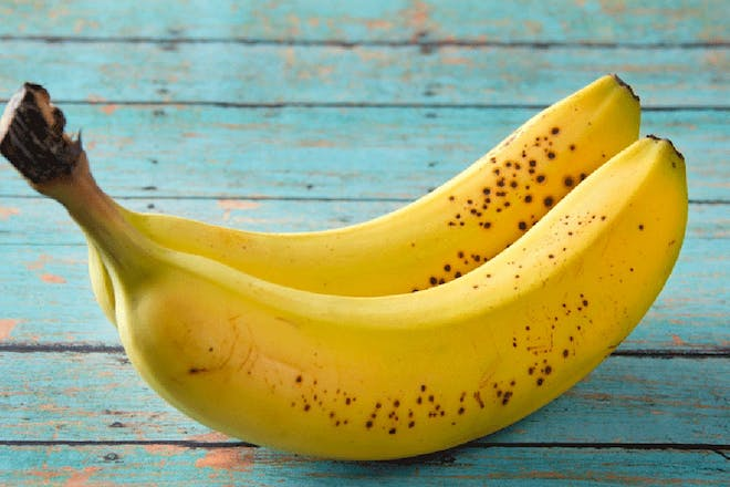 two bananas on blue wood background