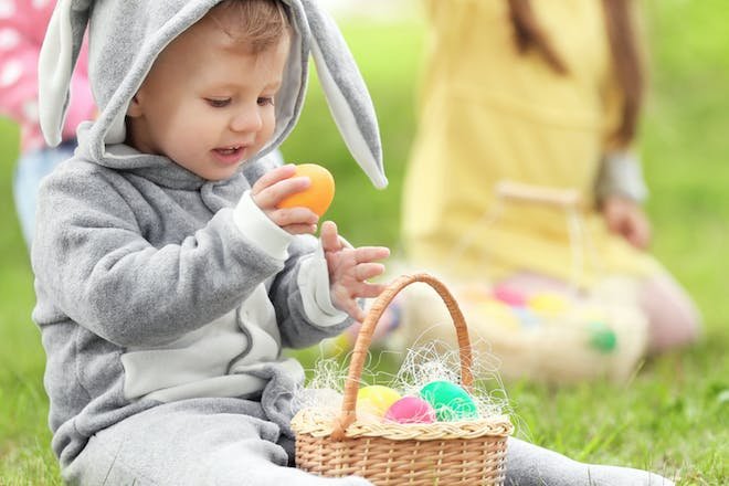 Child dressed as a bunny in an Easter egg hunt