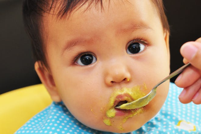 Baby with messy mouth eating puree for weaning