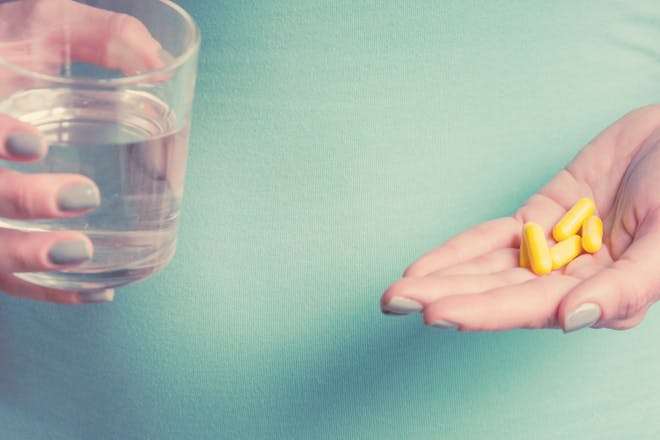 拿着杯水和一些叶酸药片的妇女