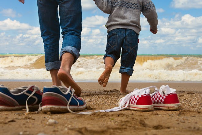 man and boy walking towards ocean with shoes on sand