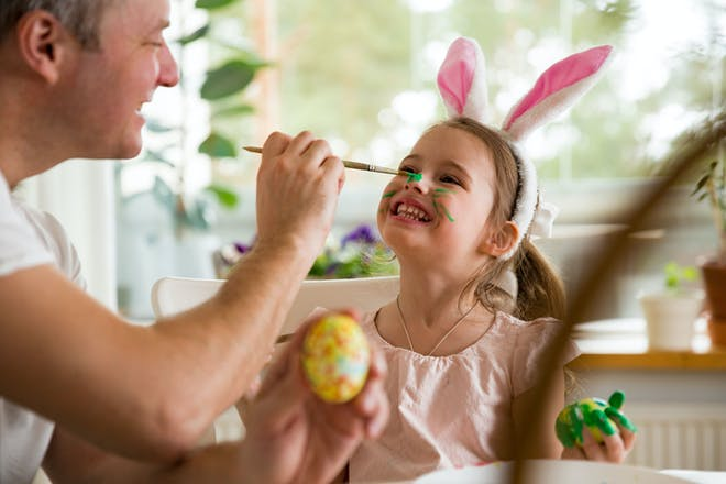 Dad face painting little girl at Easter