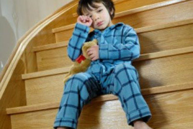 boy in blue sitting on stairs holding teddy bear