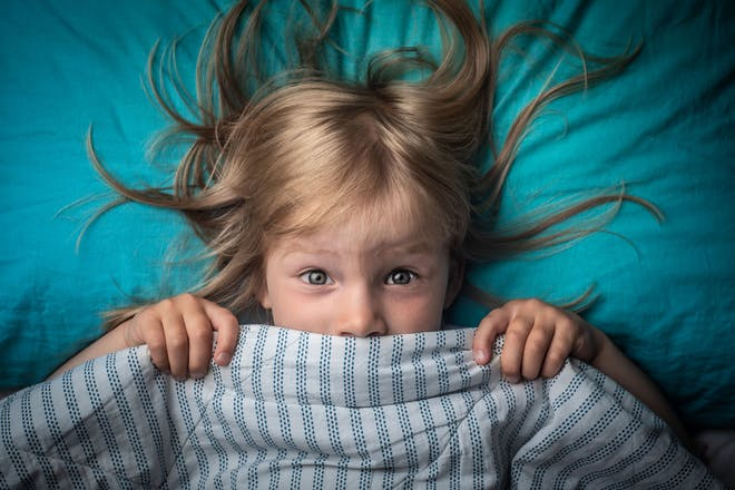 young girl in bed with covers pulled up to her face