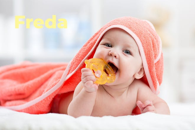 Baby with towel and chewing teething ring. Name Freda written in text