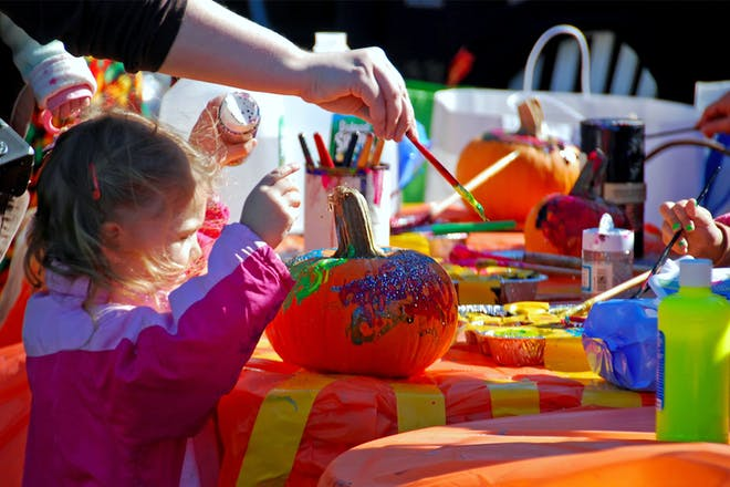 Toddler paints Halloween pumpkin at craft activities table outside