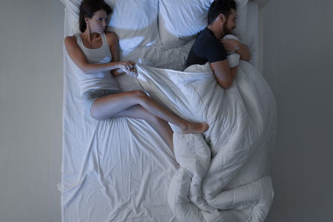 Couple in bed fighting over duvet