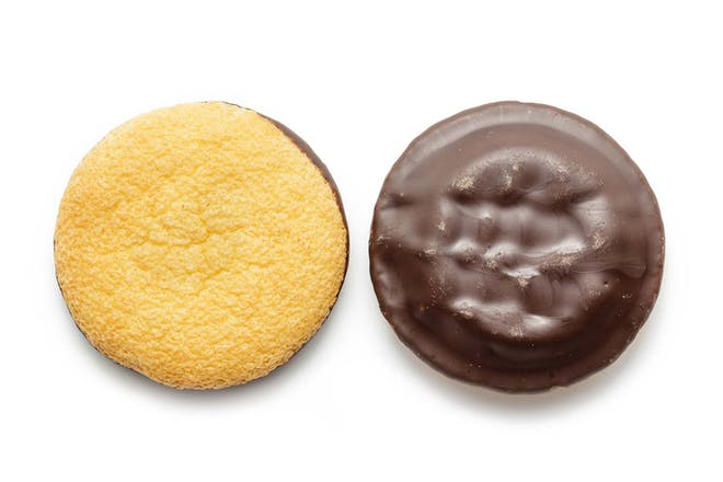 Two Jaffa Cakes on chocolate side up, one cake side up