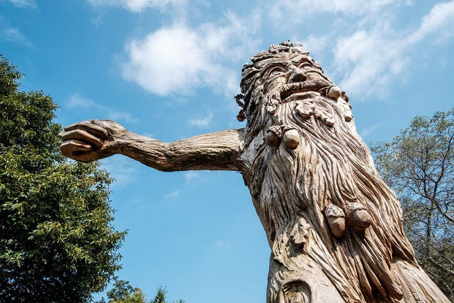 Carved wooden statue of a tree man with acorns in beard